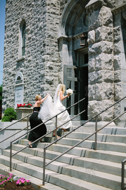 Bridesmaid holding back of bride's veil as they walk up stairs of church