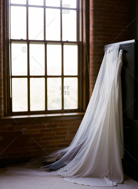 Wedding gown and veil hang on cabinet by window