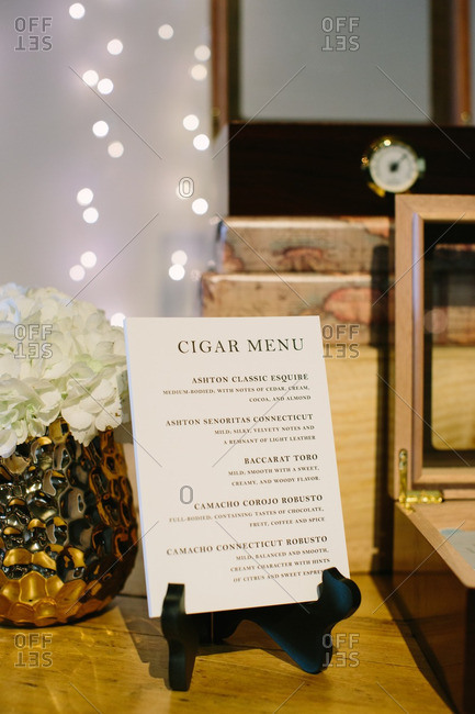 Printed cigar menu on table with boxes of cigars
