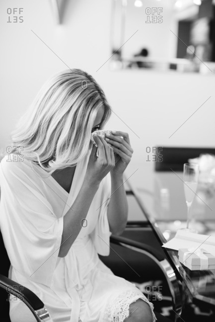 Woman wiping happy tears as she gets ready for her wedding