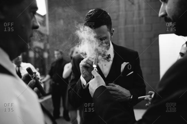 Groomsmen and guests smoking cigars