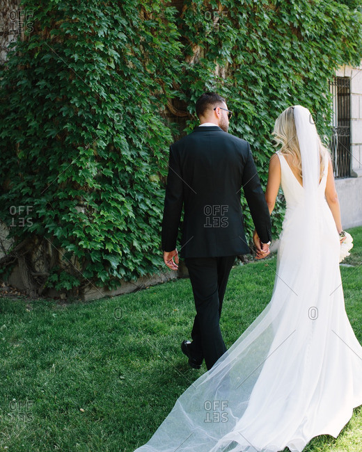 Back view of bride and groom walking hand-in-hand