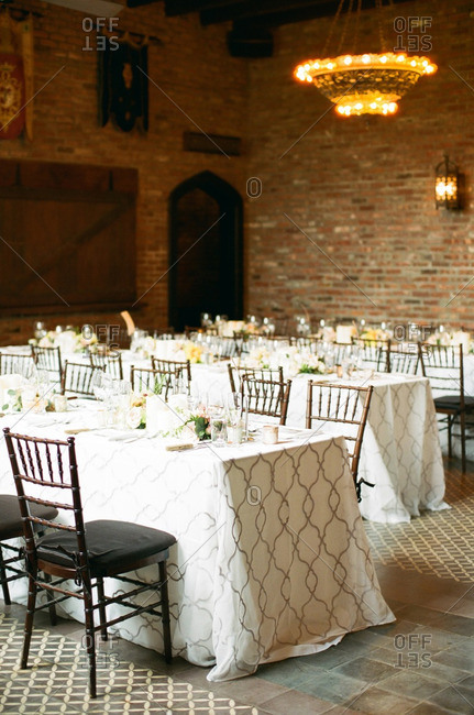 Long dining tables set for banquet in restaurant with brick walls