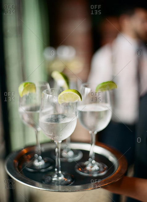 Server carrying tray of glasses of water with lime