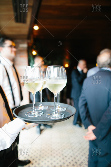 Server presents glasses of white wine to guests
