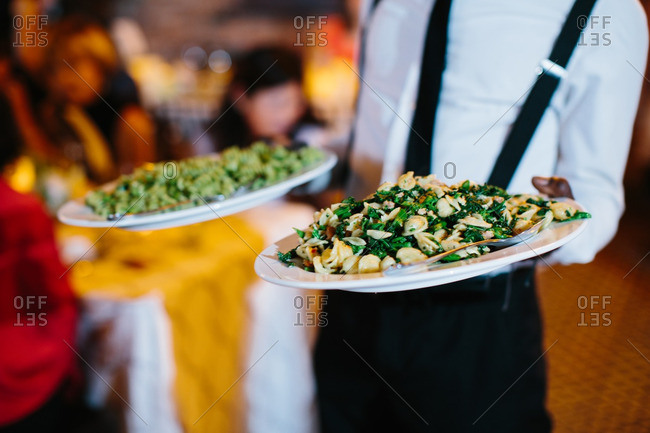 Server carries plates of pasta at restaurant