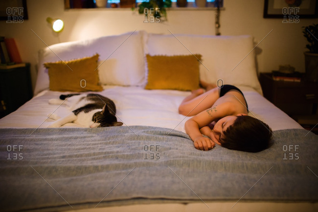 Little boy sleeping on a bed with his cat