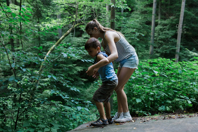 Teenage girl standing with little brother in Hocking Hills, Ohio