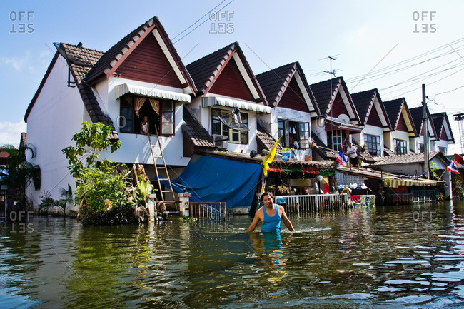 Bangkok, Thailand - November 22, 2011: Residents outside of their home in the outskirts of Bangkok Thailand during a flood