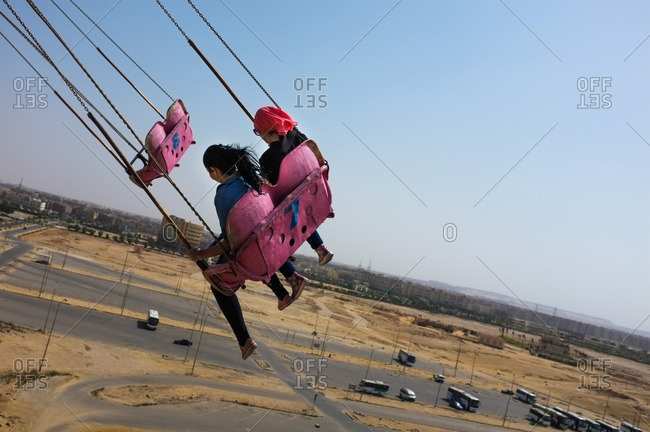 Two girls ride the swings at the Dream Park amusement park in Cairo, Egypt