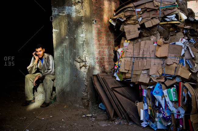 Cairo, Egypt - January 15, 2012: A garbage collector in Manshiyat Nasr takes a phone call by a pile of recycled cardboard