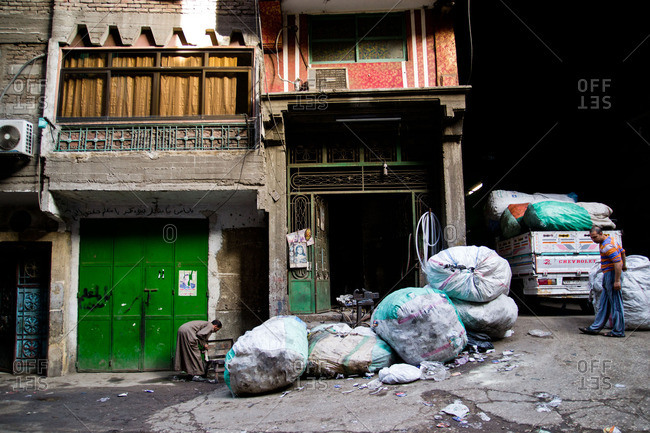 Cairo, Egypt - January 15, 2012: Bags of refuse are unloaded in the garbage collector district of Manshiyat Nasr in Cairo, Egypt