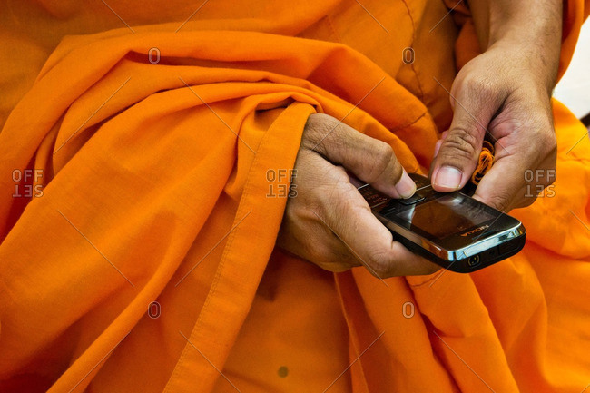 Thailand - November 27, 2011: A monk uses his cell phone in Thailand