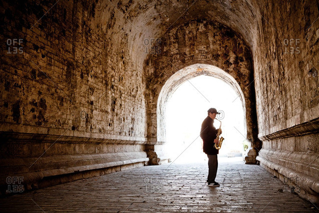 A man plays the saxophone inside of an old city wall in Nanjing, China