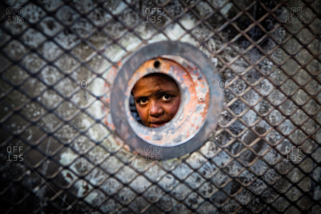Cairo, Egypt - January 3, 2013: A boy peers out from inside an abandoned military vehicle in Tahrir Square