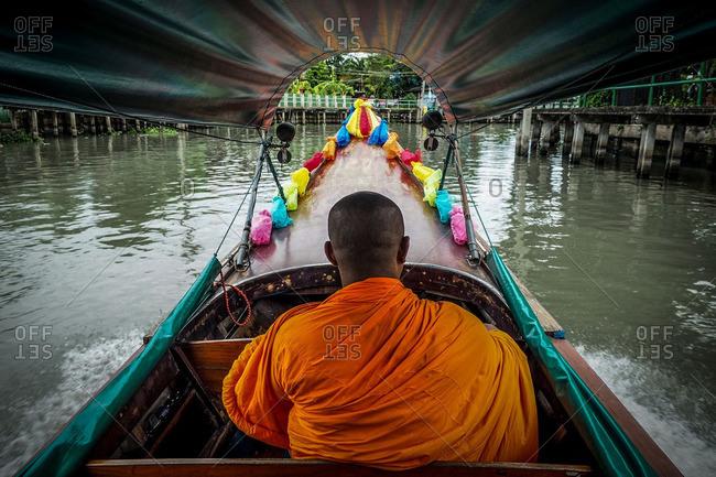 A monk rides a wooden boat along a canal in Bangkok, Thailand