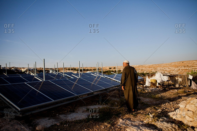 A man inspects a solar farm in the desert