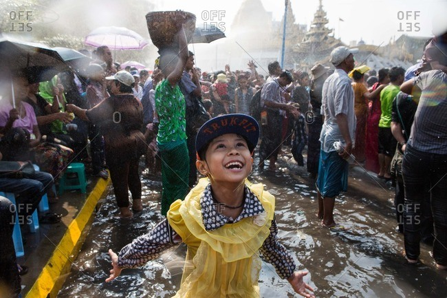 Yangon, Myanmar - April 14, 2015: A girl celebrates in the streets for Thingyan, a massive water festival symbolizing the washing away of bad luck from the previous year to usher in the traditional Burmese new year