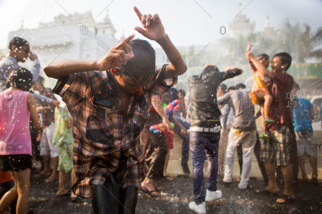 Yangon, Myanmar - April 14, 2015: People dance in the streets during Thingyan, a massive water festival symbolizing the washing away of bad luck from the previous year to usher in the traditional Burmese new year