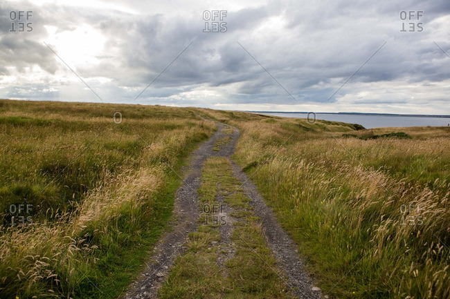 A beaten road leads towards the ocean near Caithness in the Scottish Highlands