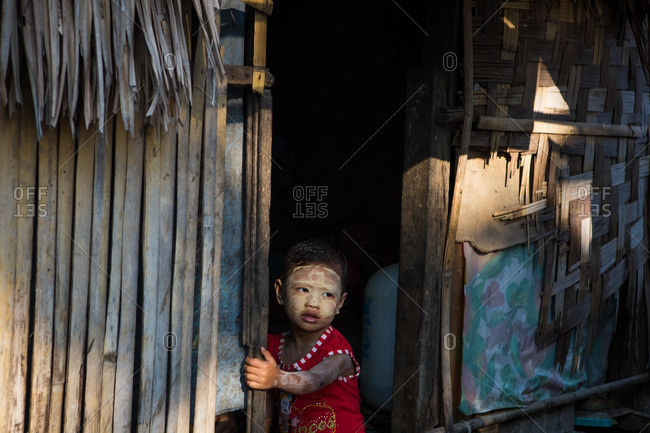 Dala township, Myanmar - December 30 2014: A girl with sun-protecting thanaka paste on her face sits in the doorway of a home