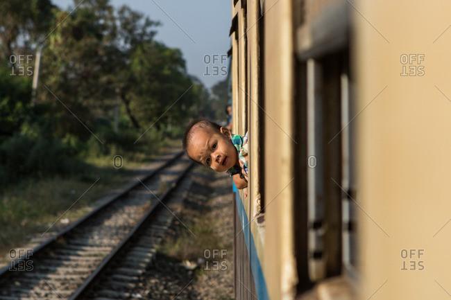 Yangon, Myanmar - January 2, 2015: A baby leaning out of a train window outside Yangon, Myanmar
