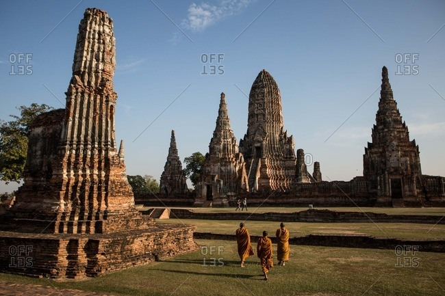 Ayutthaya, Thailand - January 14, 2015: Monks walk amongst the temple ruins of Ayutthaya