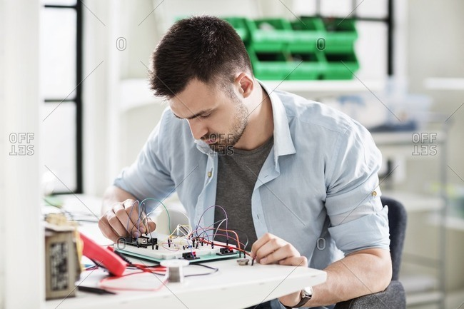 Engineer wiring circuit at table in electronics industry