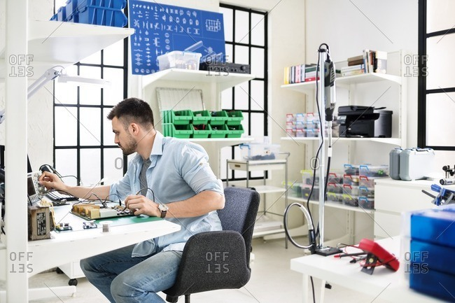 Serious technician working on circuit board at table in electronics industry