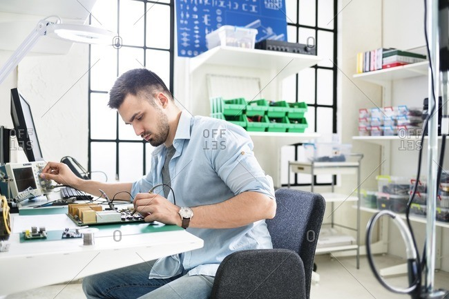 Concentrated technician soldering circuit board at table in electronics industry