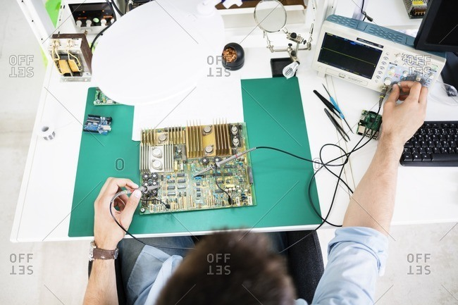 High angle view of technician checking circuit board at table in electronics industry