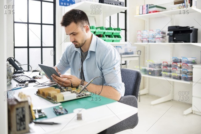 Serious engineer using tablet computer while working at table in electronics industry