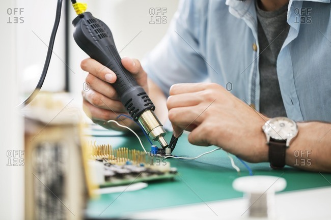 Midsection of technician working at table in electronics industry
