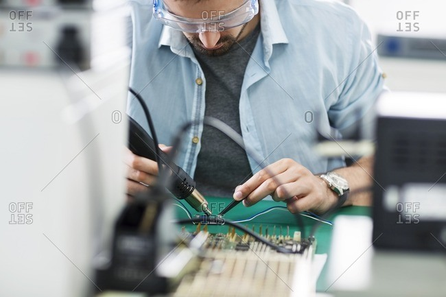 Serious technician working at table in electronics industry