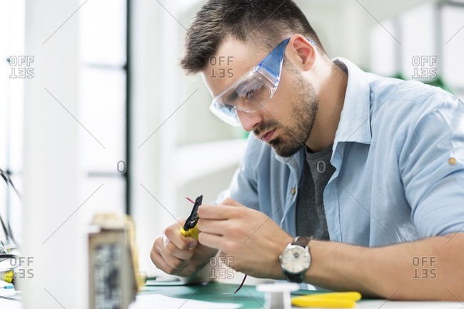 Serious technician cutting wire at table in electronics industry