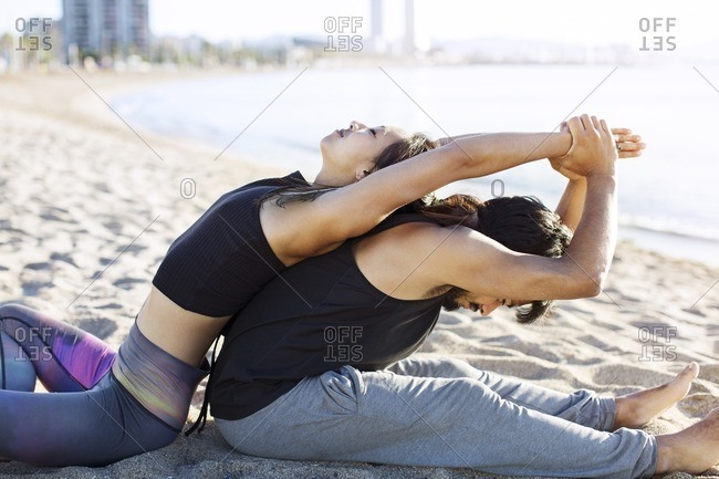 Side view of couple doing yoga together on beach