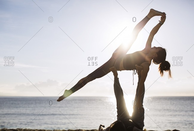Man lifting woman while performing yoga on beach against sky