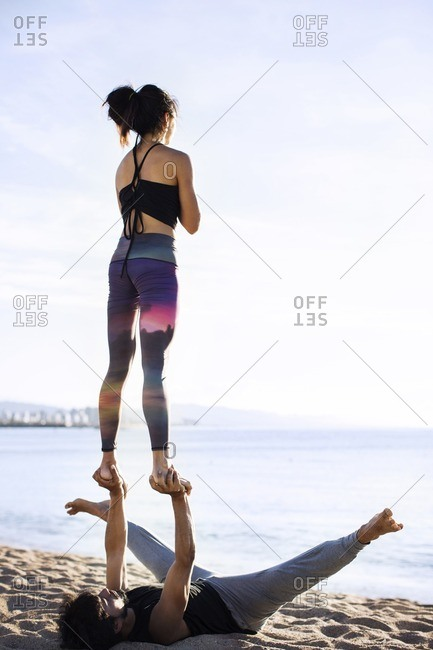 Couple performing yoga on shore against sky