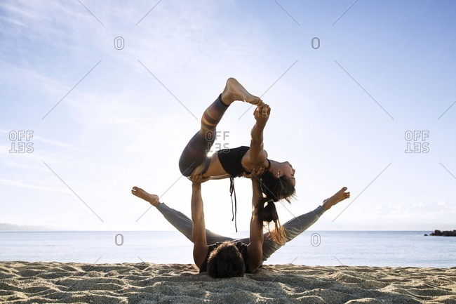 Determined couple doing yoga on shore against sky