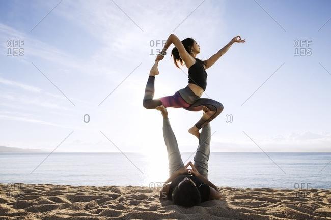 Couple doing yoga on beach against sky