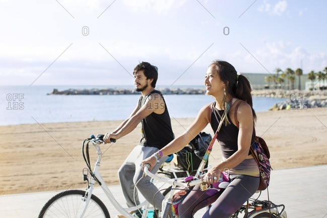 Sporty couple riding bicycles on road by beach