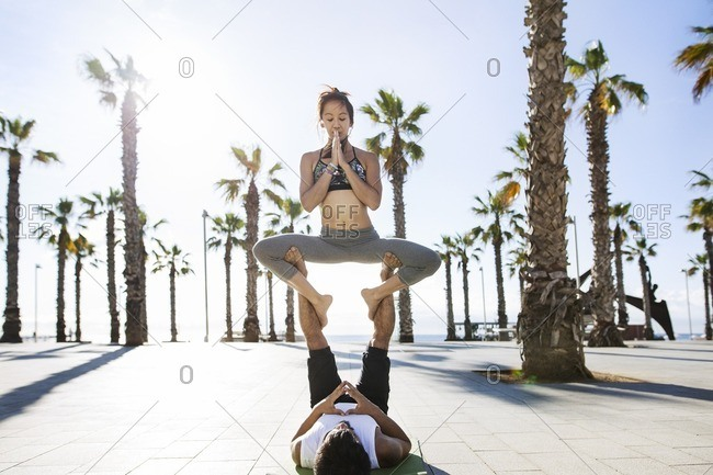 Couple performing yoga on footpath at beach during summer