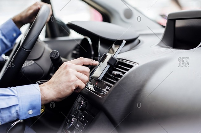 Cropped image of businessman using GPS on smart phone in car