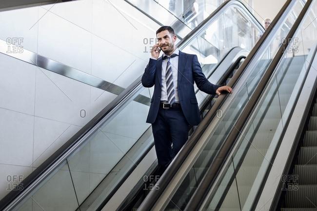 Businessman using smart phone on escalator at subway station