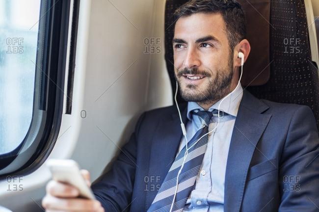 Smiling businessman listening music through smart phone in train