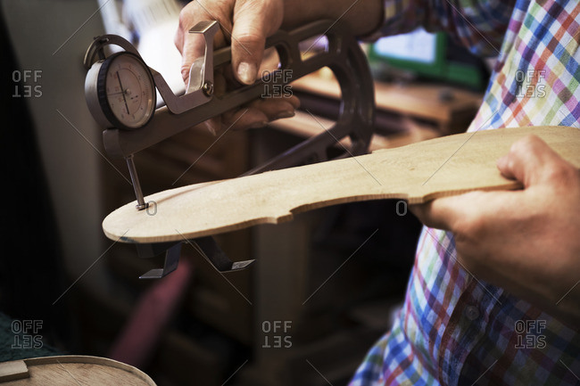 Midsection of craftsman using hand tool to measure wood at workshop