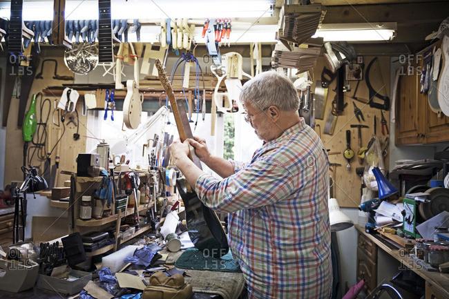 Craftsman measuring fretboard of guitar at workbench in workshop
