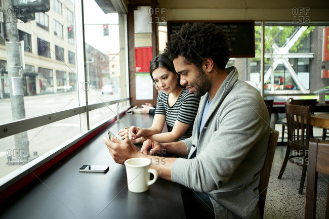 Multi-ethnic couple using tablet computer in cafe