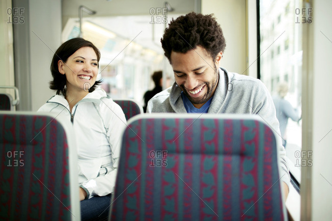 Happy multi-ethnic couple travelling in bus