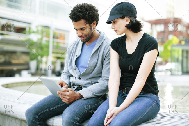 Multi-ethnic couple using tablet computer while sitting on retaining wall